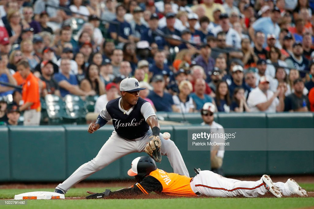 Cedric Mullins #3 of the Baltimore Orioles is safe at third base against Miguel Andujar #41 of the New York Yankees in the first inning at Oriole Park at Camden Yards on August 24, 2018 in Baltimore, Maryland.
