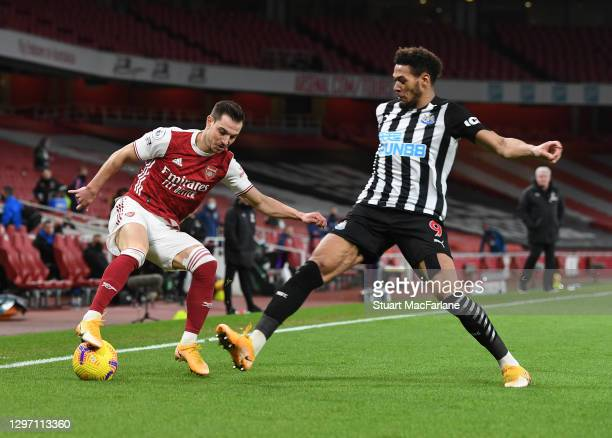 Cedric of Arsenal takes on Joelinton of Newcastle during the Premier League match between Arsenal and Newcastle United at Emirates Stadium on January...