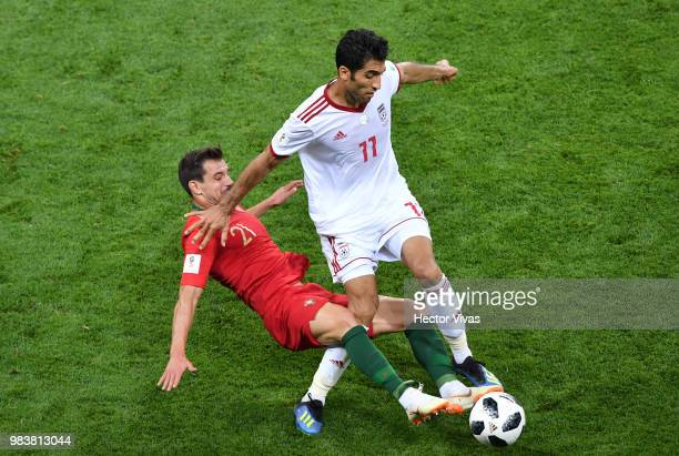Cedric of Portugal tackles Vahid Amiri of Iran during the 2018 FIFA World Cup Russia group B match between Iran and Portugal at Mordovia Arena on...
