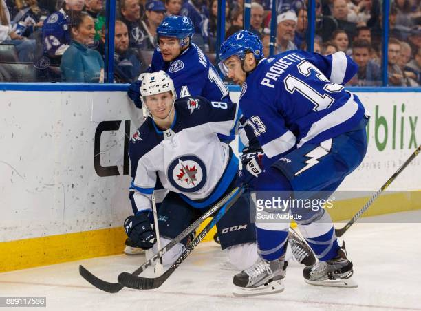 Cedric Paquette and Chris Kunitz of the Tampa Bay Lightning skate against Jacob Trouba of the Winnipeg Jets during the third period at Amalie Arena...