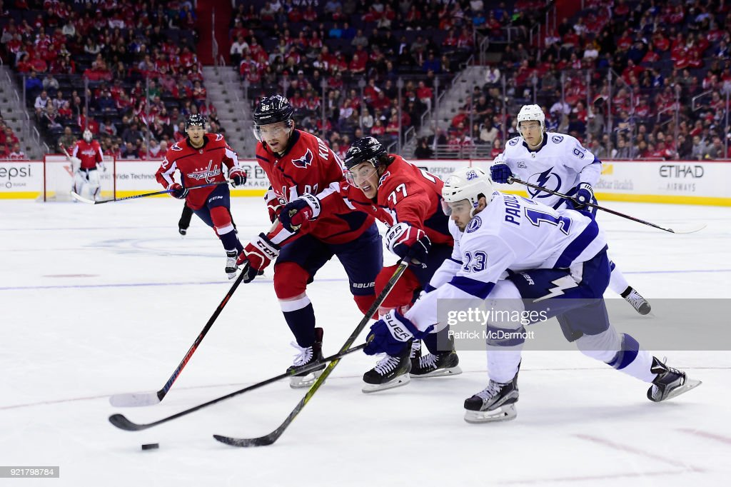 Cedric Paquette #13 of the Tampa Bay Lightning battles for the puck against T.J. Oshie #77 and Evgeny Kuznetsov #92 of the Washington Capitals in the third period at Capital One Arena on February 20, 2018 in Washington, DC.