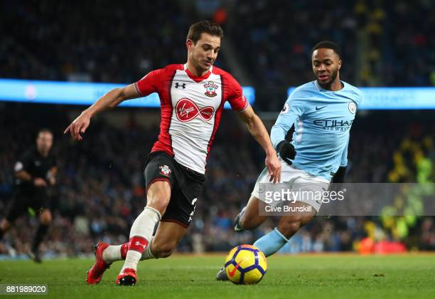 Cedric Soares of Southampton attempts to get past Raheem Sterling of Manchester City during the Premier League match between Manchester City and...