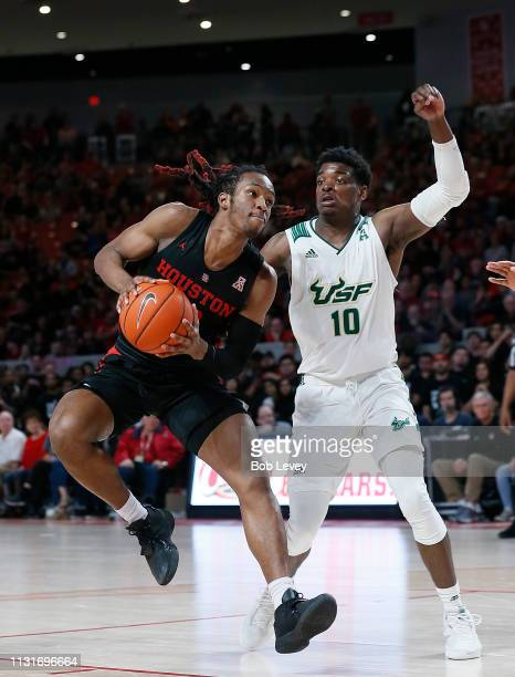 Cedrick Alley Jr #23 of the Houston Cougars drives around Alexis Yetna of the South Florida Bulls during the second half at Fertitta Center on...