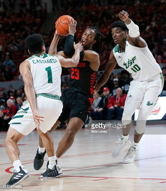 Cedrick Alley Jr #23 of the Houston Cougars drives between Xavier Castaneda of the South Florida Bulls and Alexis Yetna during the second half at...