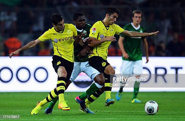 Cedrick Makiadi of Bremen is challenged by Henrikh Mkhitaryan and Nuri Sahin of Dortmund during the Bundesliga match between Borussia Dortmund and...