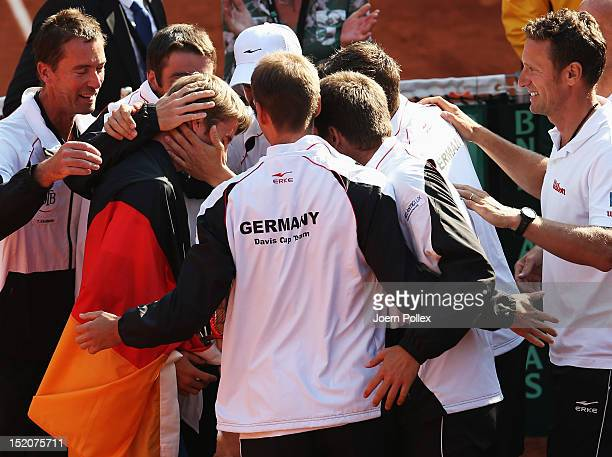 CedrikMarcel Stebe of Germany celebrates with his team after winning his match against Lleyton Hewitt of Australia during the Davis Cup World Group...