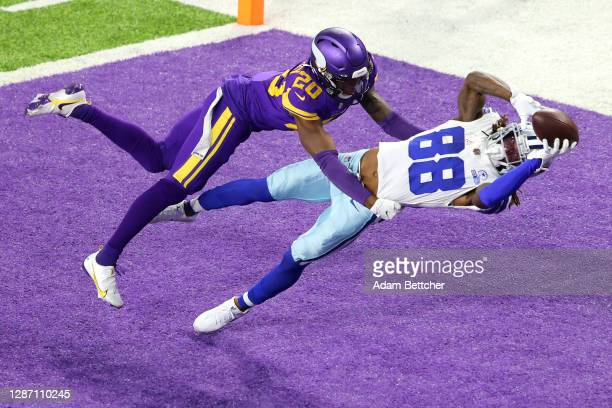 CeeDee Lamb of the Dallas Cowboys pulls in a touchdown pass against Jeff Gladney of the Minnesota Vikings during their game at U.S. Bank Stadium on...