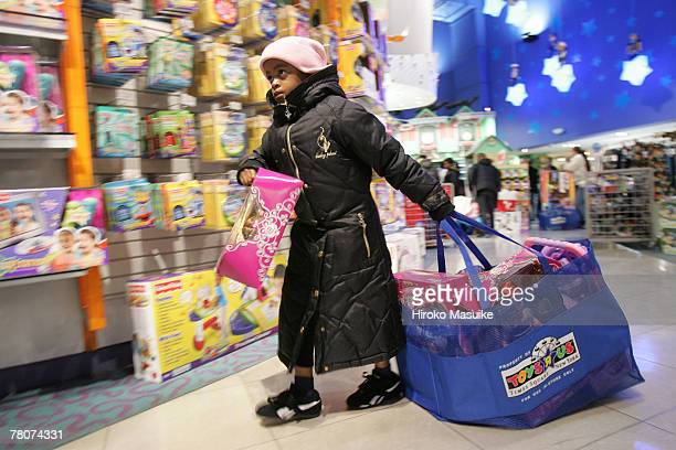 Ceilene Gonzalez 6yearsold carries a bag with toys as she shops with her mother at the Toys 'R' Us in Times Square November 23 2007 in New York City...
