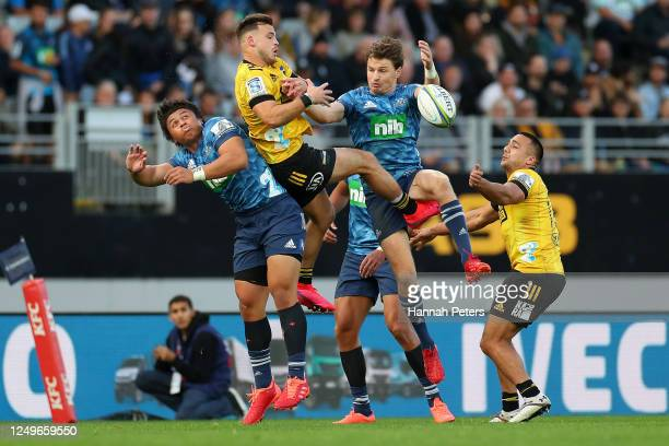 Celeb Clarke and Beauden Barrett of the Blues compete in the air with Wes Goosen and Chase Tiatia of the Hurricanes during the round 1 Super Rugby...