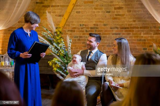 celebrant performing naming ceremony for parents and their baby daughter in an historic barn. - ceremony stock pictures, royalty-free photos & images