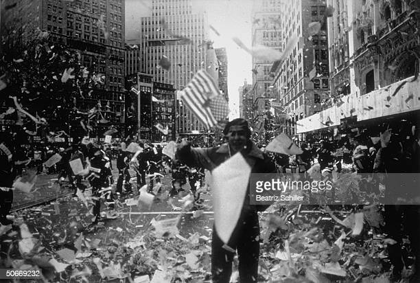 Celebrant waving flag amid shower of confetti during ticker tape parade on lower Broadway feting release of American hostages after 444 days of...