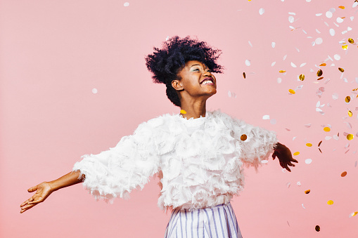 Celebrate happiness and joy- young girl throwing confetti 980390320