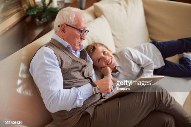 celebrating christmas, grandfather sharing a digital tablet with his grandson. - storia foto e immagini stock