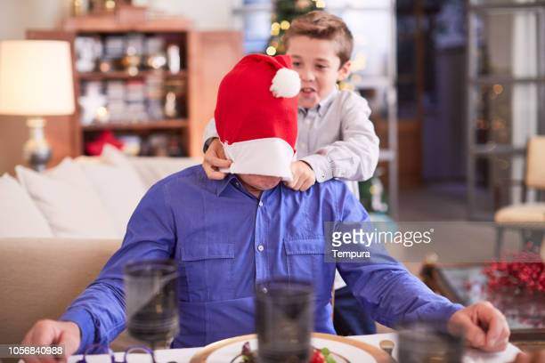 celebrating christmas, grandson covering grandad's eyes with a christmas hat. - naughty santa stock photos and pictures