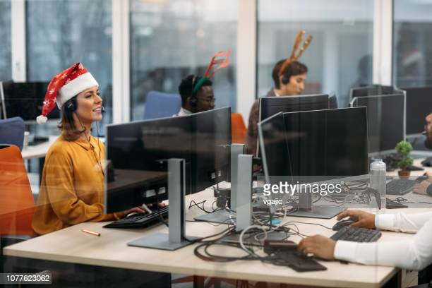 celebrating christmas in call center office. - santa hat stock photos and pictures