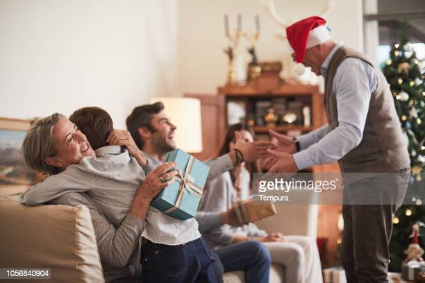 celebrating christmas, opening christmas presents. - giving stock pictures, royalty-free photos & images