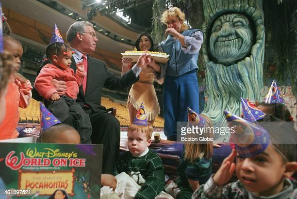 Celebrating his birthday party at the FleetCenter Mayor Thomas M Menino receives a cake from Pocahontas and John Smith after reading the story to the...