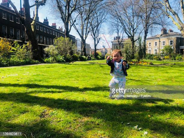 celebrating spring outside - happy little boy dancing on the lawn - one baby boy only stock pictures, royalty-free photos & images