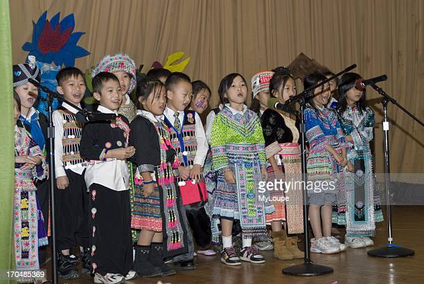 Celebrating the Hmong New Year Hmong language and culture charter school St Paul Minnesota United States 2nd grade students in traditional dress sing...