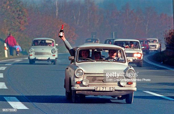 Celebrating the opening of the border between East and West Germany a smiling man holds a bottle of sparkling wine out of the window of a Trabant car...