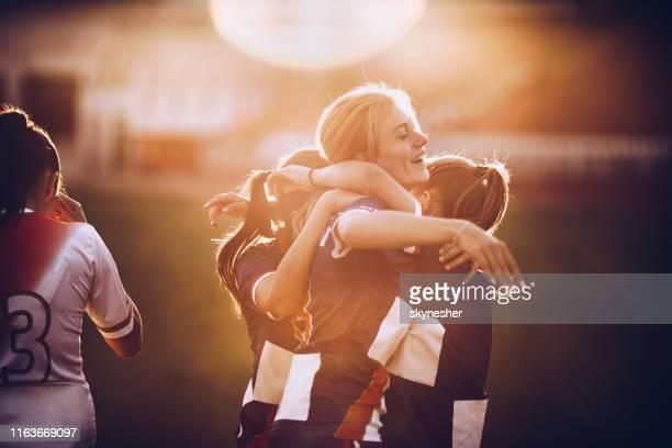 feiern sie den sieg nach dem fußballspiel! - frauenfußball stock-fotos und bilder