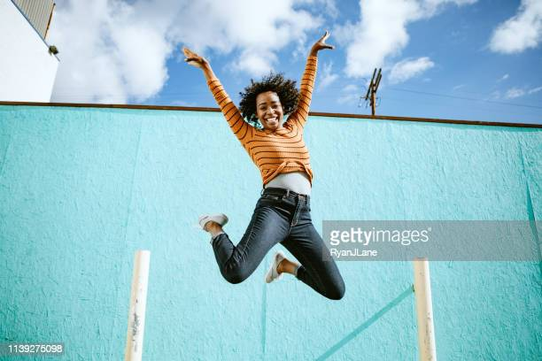 celebrating woman jumps into the air - mid air stock pictures, royalty-free photos & images