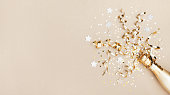 Celebration background with golden champagne bottle, confetti stars and party streamers. Christmas, birthday or wedding concept. Flat lay.