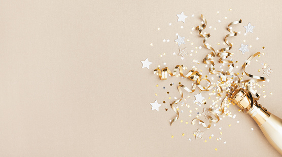 Celebration background with golden champagne bottle, confetti stars and party streamers. Christmas, birthday or wedding concept. Flat lay. 1180973713