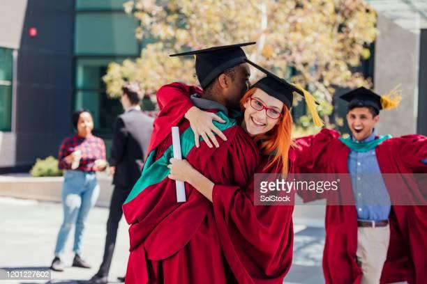 celebration embrace - alumni stock pictures, royalty-free photos & images