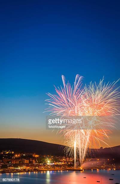 Celebration fireworks exploding in blue sunset sky over seaside town