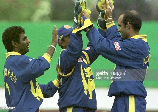 Celebration for the Sri Lanka team as Muthiah Muralitharan and wicket keeper Romesh Kaluwitharana congratulate Mavan Attapattu for catching out David...