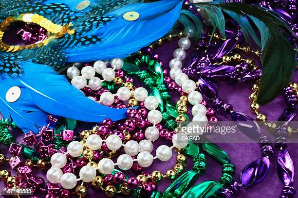 celebration mask background with beads and feathers - mardi gras party stock photos and pictures