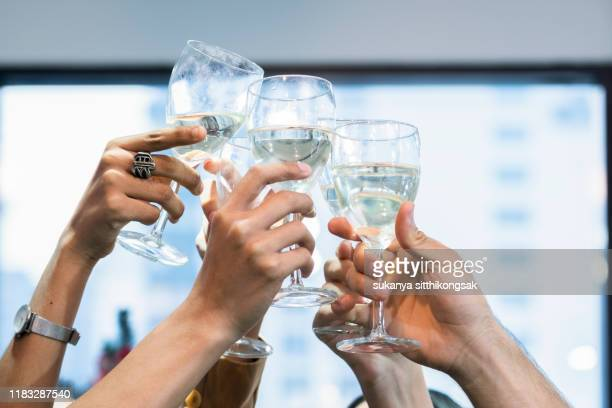 celebration of friends holding a glass of champagne to celebrate friendship and success in working as a team. - graduation background stock pictures, royalty-free photos & images