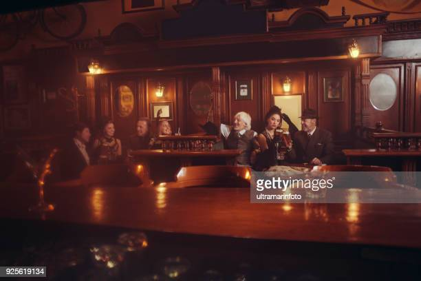 celebration retro pub old-fashioned group of senior men and young woman drinking beer party - pub stock pictures, royalty-free photos & images