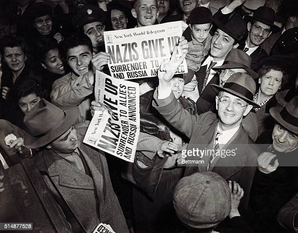 Celebrations begin in New York on the announcement of Germany's surrender at the end of World War II 7th May 1945 People are holding up copies of the...