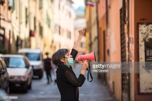 Celebrations in Bologna of Liberation Day on April 25 2020 in Bologna Italy A woman singing Bella Ciao song from the street while people are singing...