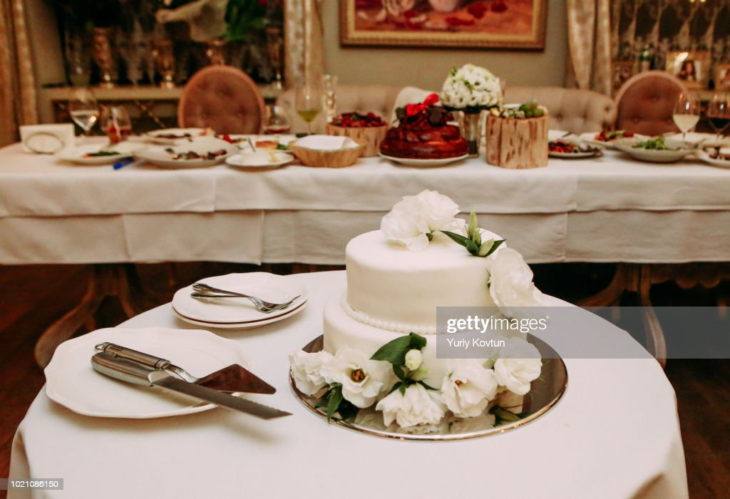 celebratory cake white on a table with cutlery : Foto de stock