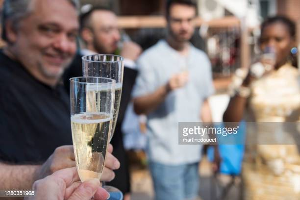 """celebratory toast at wedding cocktail in backyard. - """"martine doucet"""" or martinedoucet stock pictures, royalty-free photos & images"""