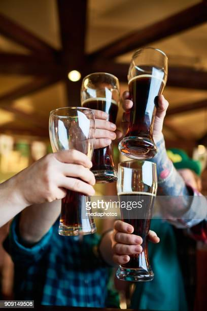 celebratory toast with pints of stout beer - st patricks day stock pictures, royalty-free photos & images
