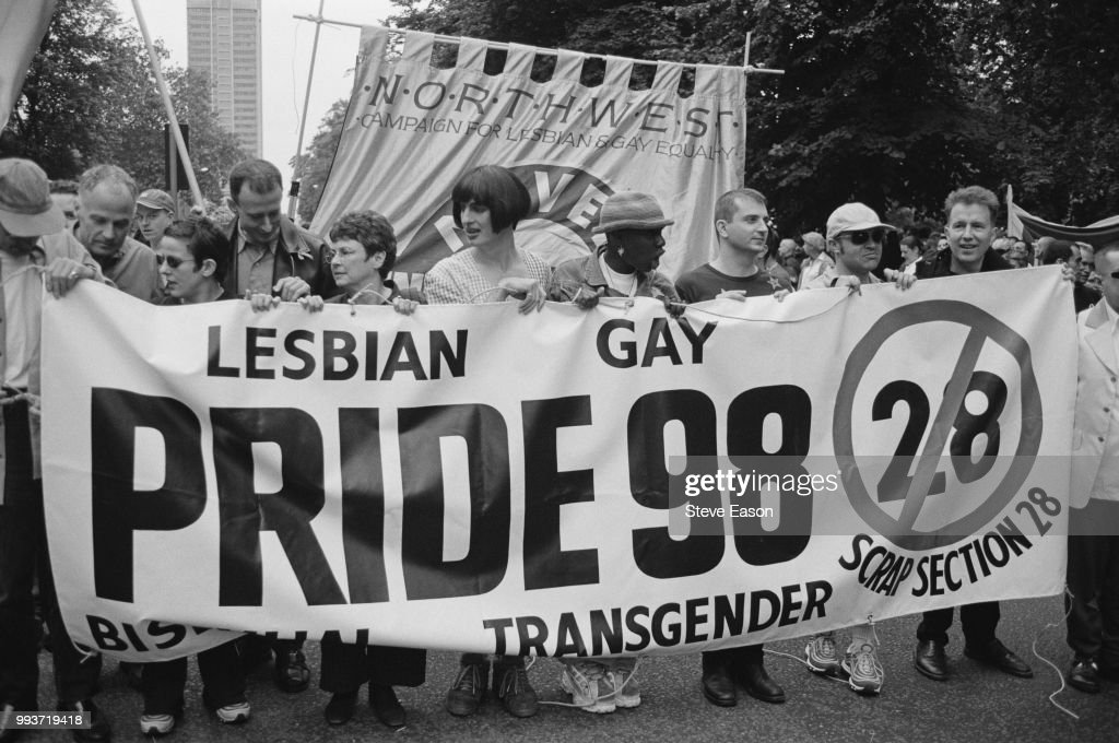 Celebrities help to hold a banner opposing Section 28, at the Lesbian, Gay, Bisexual, and Transgender Pride event, London, 4th July 1998. Those present include (from second left) actor Michael Cashman, comedian Rhona Cameron and activist Peter Tatchell. First and second from right are musician and radio presenter Tom Robinson, and comedian and TV presenter Graham Norton. Section 28 was an amendment to the Local Government Act 1988, passed by the British parliament the previous May and forbidding the 'promotion' of homosexuality by local authorities. It was repealed in 2003.