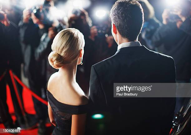 celebrities posing for paparazzi on red carpet - evening gown stock photos and pictures