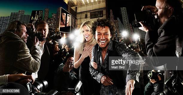 Celebrities walking through paparazzi