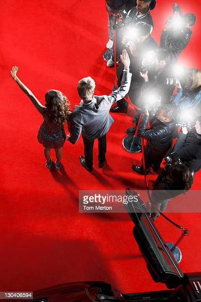 Celebrities waving to paparazzi on red carpet