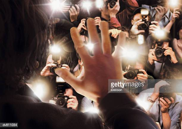 celebrity being photographed by a large group of paparazzi - adulation stock pictures, royalty-free photos & images