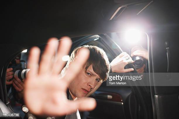 celebrity blocking photo in backseat of limo - celebrities photos stock pictures, royalty-free photos & images