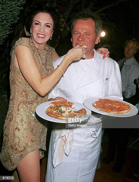 Celebrity chef Wolfgang Puck and his wife Barbara Lazaroff show off their trademark pizzas at the Spago closing party March 28 2001 in West Hollywood...