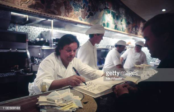 Celebrity chef Wolfgang Puck signs copy of his cook book at counter his restaurant Spago in Los Angeles California USA circa 1986