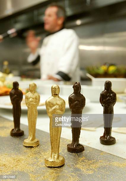 Celebrity Chef Wolfgang Puck talks the media behind some gold dusted chocolate oscars during the Oscars 2004 Governors Ball Food and Decor Preview at...