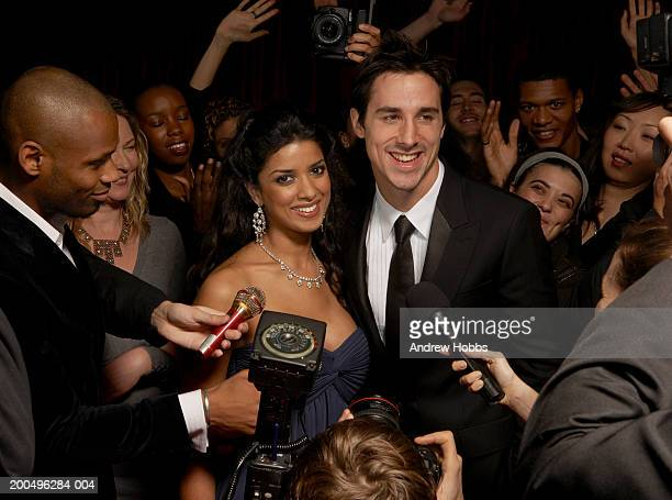 Celebrity couple in evening wear talking to fans and media at event