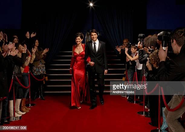 Celebrity couple in evening wear walking on red carpet